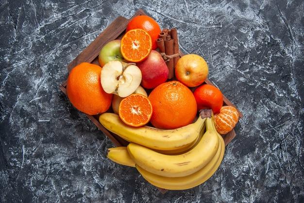 Vista superior de frutas frescas cortadas y palitos de canela en bandeja de madera en la mesa