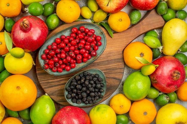 Vista superior de frutas frescas diferentes frutas maduras y suaves en el escritorio blanco
