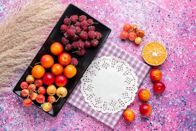 Vista superior de frutas frescas frambuesas y ciruelas dentro de forma negra sobre la superficie rosa