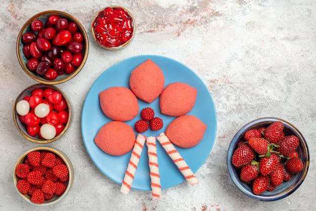 Vista superior de frutas frescas, frambuesas, fresas y cornejos con galletas en el escritorio blanco
