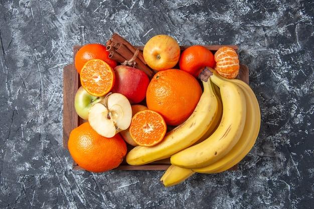 Vista superior de frutas frescas y palitos de canela en bandeja de madera en la mesa