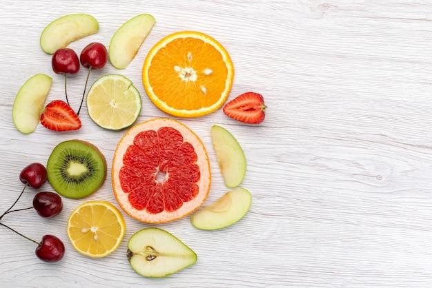 Una vista superior de frutas frescas en rodajas suaves y maduras en el escritorio blanco, fruta fresca de color vitamina