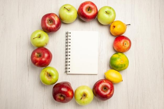 Vista superior de frutas frescas suaves y maduras en el escritorio blanco, frutas de la planta, árbol verde fresco de color Foto gratis