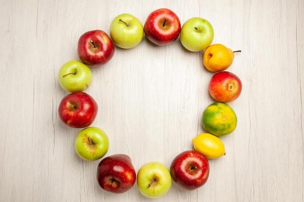 Vista superior de frutas frescas suaves y maduras en el escritorio blanco, frutas de la planta, árbol verde fresco de color