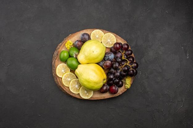 Vista superior frutas frescas uvas rodajas de limón ciruelas y membrillos en la superficie oscura planta de árbol de frutas maduras frescas