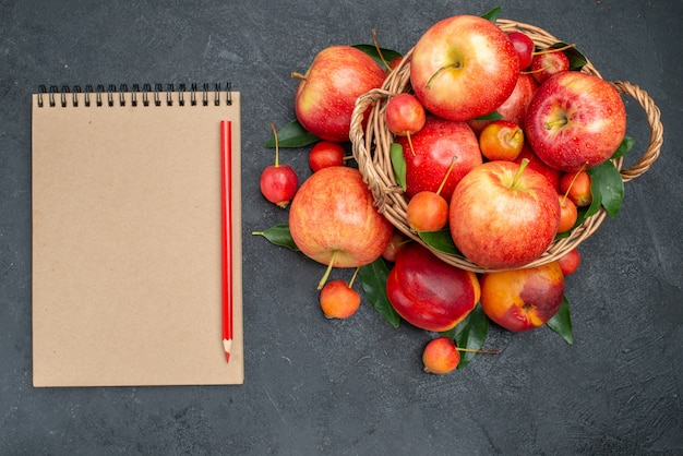 Vista superior frutas frutas y bayas con hojas en la cesta de madera lápiz de cuaderno crema