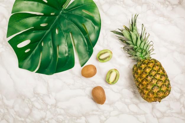 Vista superior frutas y hoja tropicales sobre mármol