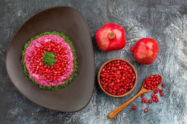 Vista superior de frutas lejanas un plato apetitoso con hierbas granadas semillas de cuchara de granada