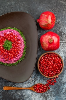 Vista superior de frutas lejanas semillas de granada cuchara un plato apetitoso