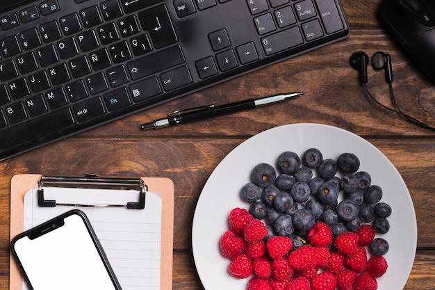 Vista superior de frutas en placa y teclado con cuaderno en blanco y teléfono