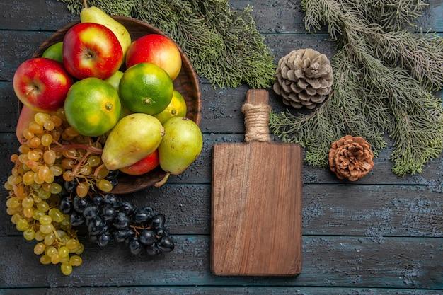 Vista superior frutas y ramas uvas blancas y negras limas peras manzanas en un tazón junto a ramas de abeto tabla de cortar y conos en superficie gris