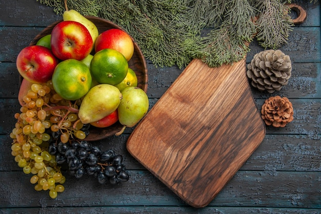 Vista superior de frutas y ramas, uvas blancas y negras, limas, peras, manzanas en un tazón junto a ramas de abeto, tablero de cocina y conos en la mesa oscura.