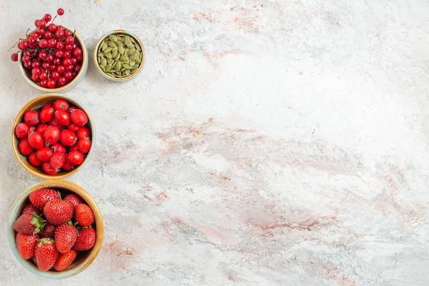Vista superior de frutas rojas frescas en mesa blanca fruta fresca