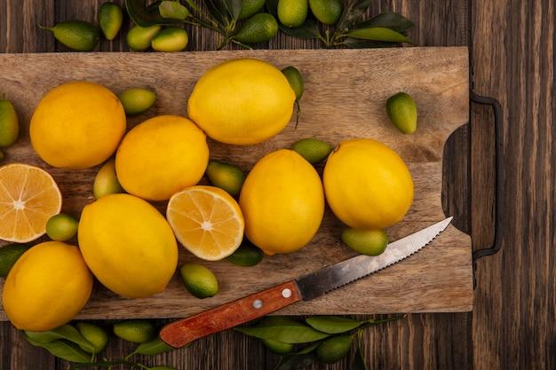 Vista superior de frutas saludables como kinkans y limones en una tabla de cocina de madera con un cuchillo sobre una superficie de madera