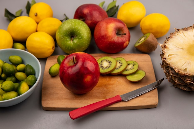 Vista superior de frutas saludables como rodajas de kiwi de manzana y kinkans en una tabla de cocina de madera con un cuchillo con kinkans en un recipiente con coloridas manzanas, limones y piña aislado sobre un fondo blanco.