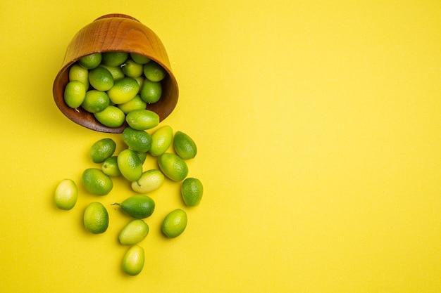 Vista superior de las frutas en un tazón de fuente de las apetitosas frutas verdes en el tabl
