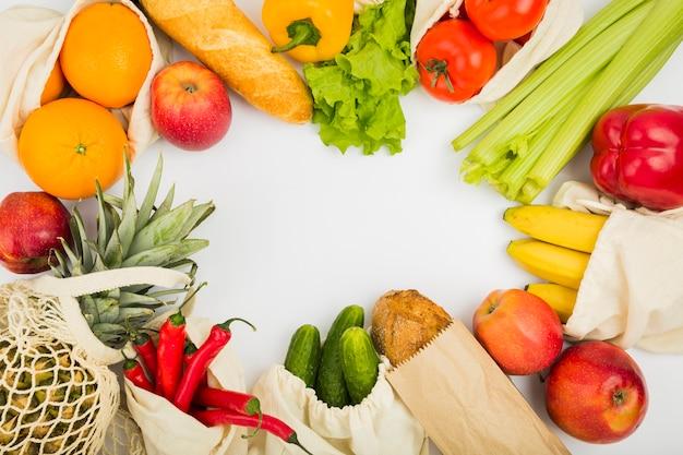 Vista superior de frutas y verduras en bolsas reutilizables.