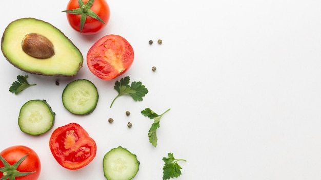 Vista superior de frutas y verduras sobre fondo blanco.