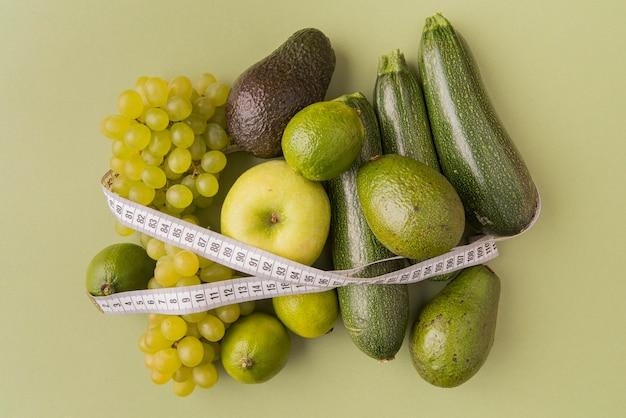 Vista superior de frutas y verduras verdes atadas con cinta métrica