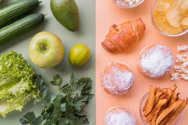 Vista superior de frutas y verduras verdes con merienda poco saludable
