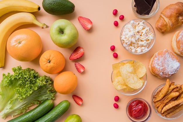Vista superior de frutas y verduras versus refrigerios poco saludables