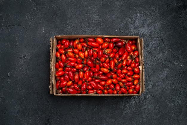 Vista superior de frutos rojos maduros y bayas agrias en superficie gris