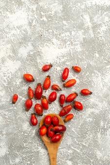 Vista superior de frutos rojos secos en superficie blanca color seco de frutas