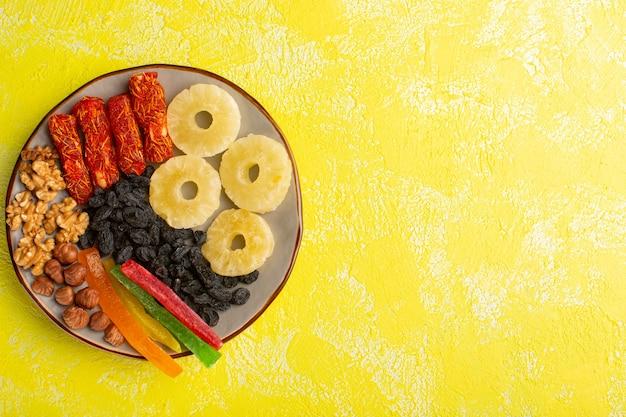 Vista superior de frutos secos, anillos de piña, nueces y turrón