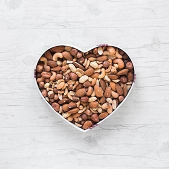 Vista superior de frutos secos en forma de corazón en escritorio de madera