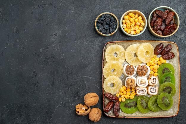 Vista superior de frutos secos en rodajas anillos de piña y kiwis sobre fondo gris frutos secos pasas vitamina dulce salud agria