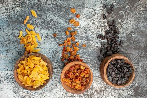 Vista superior de los frutos secos tres cuencos marrones de los apetitosos frutos secos de colores