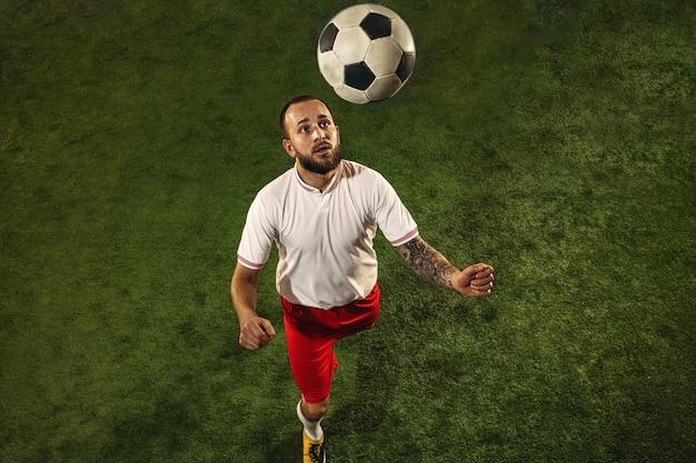 Vista superior del fútbol o jugador de fútbol sobre hierba verde