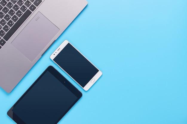 Vista superior de gadgets sobre fondo azul, la composición de una computadora portátil, auriculares blancos, teléfono, vaso con una bebida y llaves del automóvil
