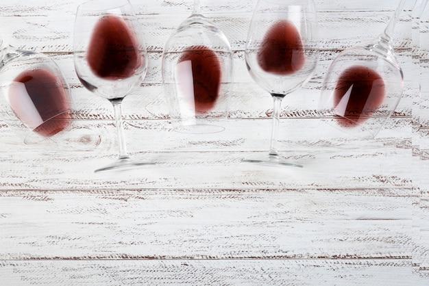 Vista superior de gafas puesta sobre la mesa con vino tinto