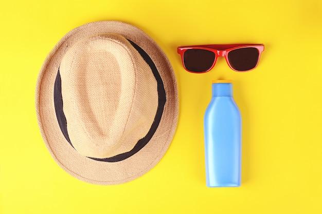 Vista superior de gafas de sol, bloqueador solar y sombrero.
