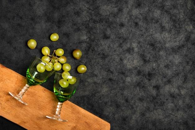 Vista superior gafas con uvas sobre fondo de pizarra