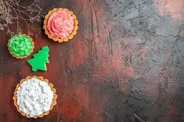 Vista superior de la galleta del árbol de navidad y diferentes tartas en la superficie de color rojo oscuro