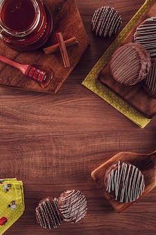 Vista superior de la galleta de miel brasileña cubierta de chocolate sobre la mesa de madera con miel de abeja y canela - pã £ o de mel