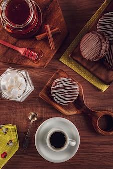 Vista superior de la galleta de miel cubierta de chocolate sobre la mesa de madera con café, miel de abeja y terrones de azúcar - pã £ o de mel