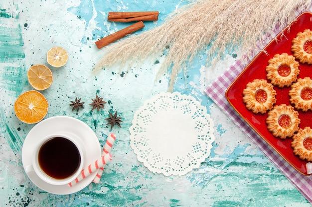 Vista superior de las galletas de azúcar dentro de la placa roja con una taza de té sobre el fondo azul.