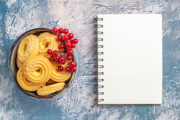 Vista superior de galletas de azúcar con frutos rojos sobre superficie azul claro