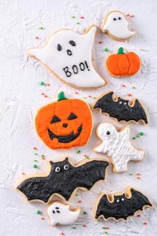 Vista superior de las galletas de azúcar de jengibre glaseado decoradas festivas de halloween sobre fondo blanco con espacio de copia y diseño plano.