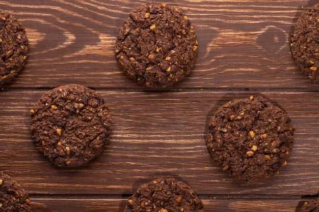 Vista superior de galletas de chispas de chocolate con cereales, nueces y cacao en madera