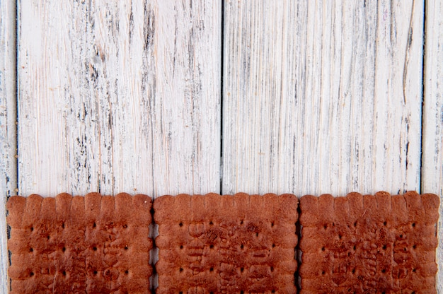 Vista superior galletas de chocolate en la parte inferior con espacio de copia sobre fondo blanco de madera