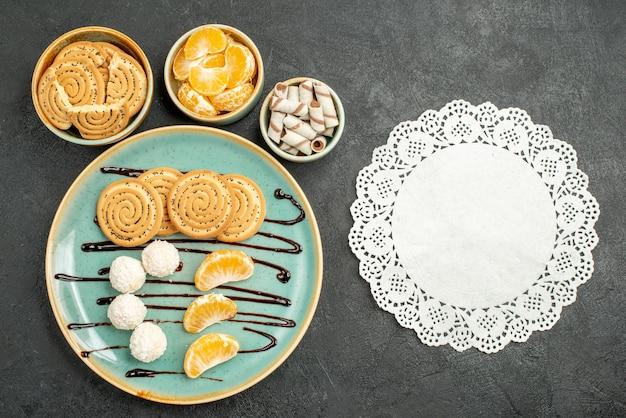Vista superior de galletas dulces con caramelos de coco sobre fondo gris