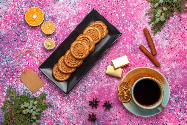 Vista superior de galletas dulces dentro de forma negra con canela y té en superficie rosa claro