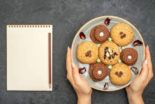 Vista superior de las galletas dulces dentro de la placa sobre fondo gris oscuro, galleta de azúcar, galleta dulce, pastel de té