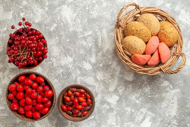 Vista superior de galletas dulces con frutos rojos sobre fondo blanco.