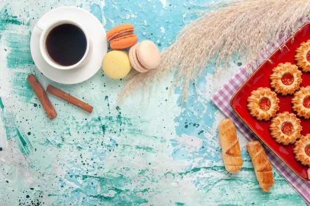 Vista superior de galletas dulces con macarons de bagels y taza de té sobre fondo azul claro
