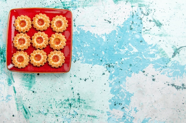 Vista superior de galletas dulces con mermelada de naranja dentro de la placa roja sobre fondo azul.